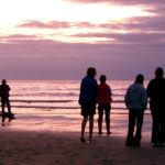 People-on-shoreline-at-sunset